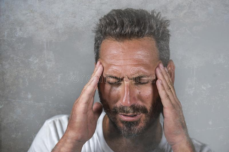 Close up dramatic  portrait of young attractive anxious and depressed man in pain with hands on his head suffering headache and royalty free stock image