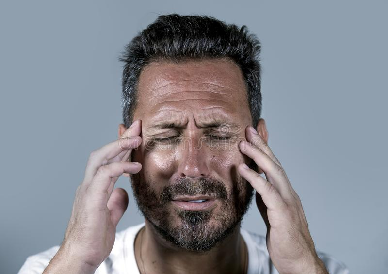 Close up dramatic  portrait of young attractive anxious and depressed man in pain with hands on his head suffering headache and royalty free stock photography