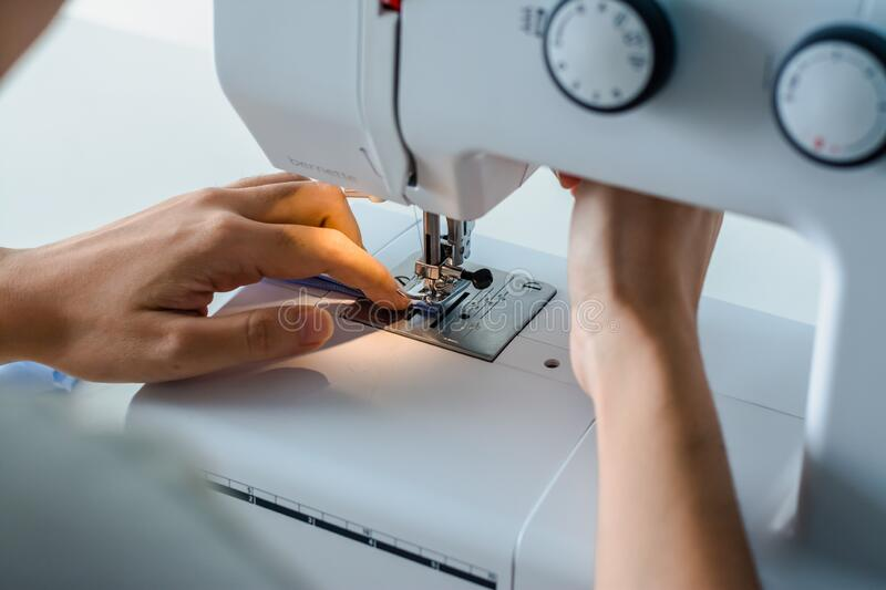 Close up dressmaker is process electric sewing machine with fabric and thread ,starting for tailor business. Close up dressmaker is process electric sewing stock image