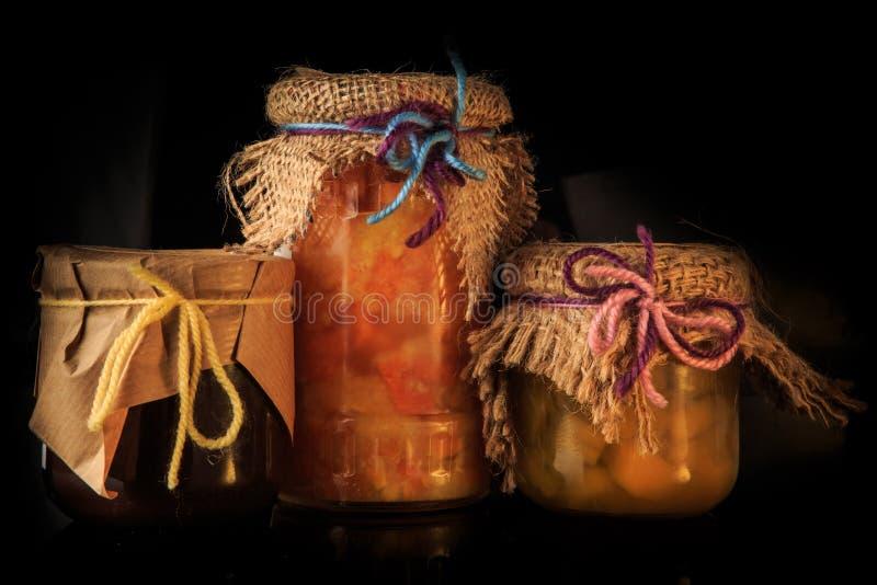 close-up drie glaskruiken natuurlijke jam met rustieke decoratie royalty-vrije stock afbeelding