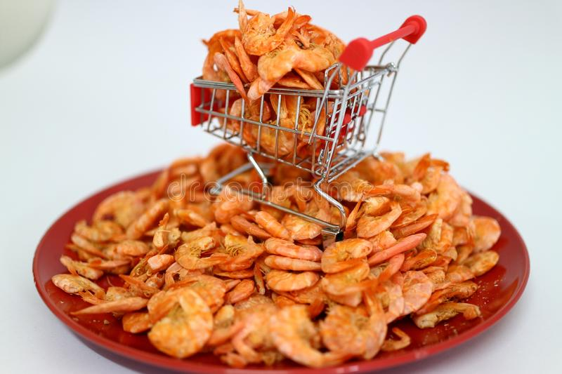 Close-up of dried shrimp on a shopping car about online dried seafood trading business  White background. Close-up dried shrimp shopping car online seafood royalty free stock image