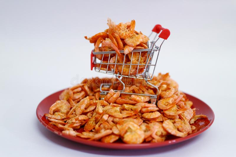 Close-up of dried shrimp on a shopping car about online dried seafood trading business  White background. Close-up dried shrimp shopping car online seafood stock image