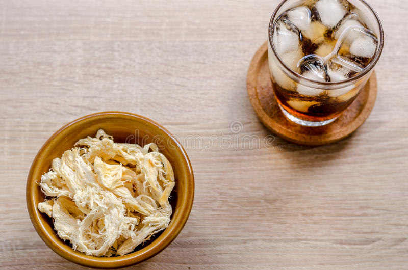 Close up in dried squid and cola in glass on wooden background stock photo