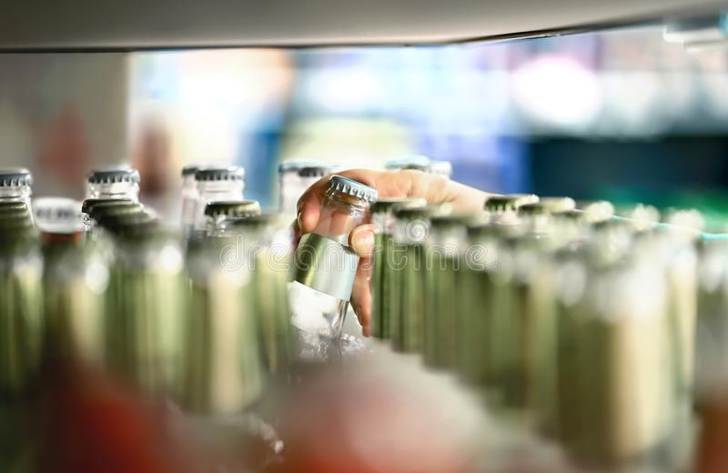 Close up of drink shelf in supermarket. Alcohol, soda, sodapop, mineral water or ginger ale bottle. Customer buying product. royalty free stock photography