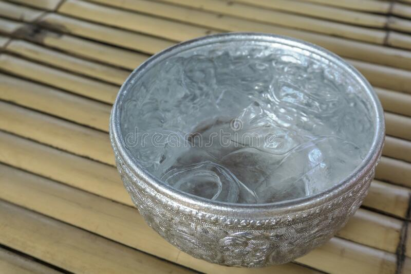 Close up Drinking water and ice cube in metal bowl, Thai traditional container. Drinking water and ice cube in metal bowl, Thai traditional container royalty free stock image