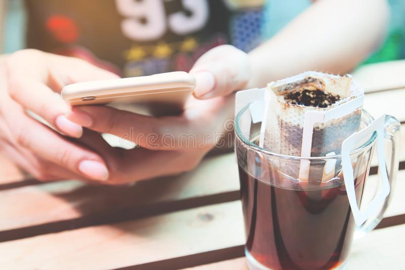 Close up drip coffee with woman using smartphone, Lifestyle, Online shopping royalty free stock photos