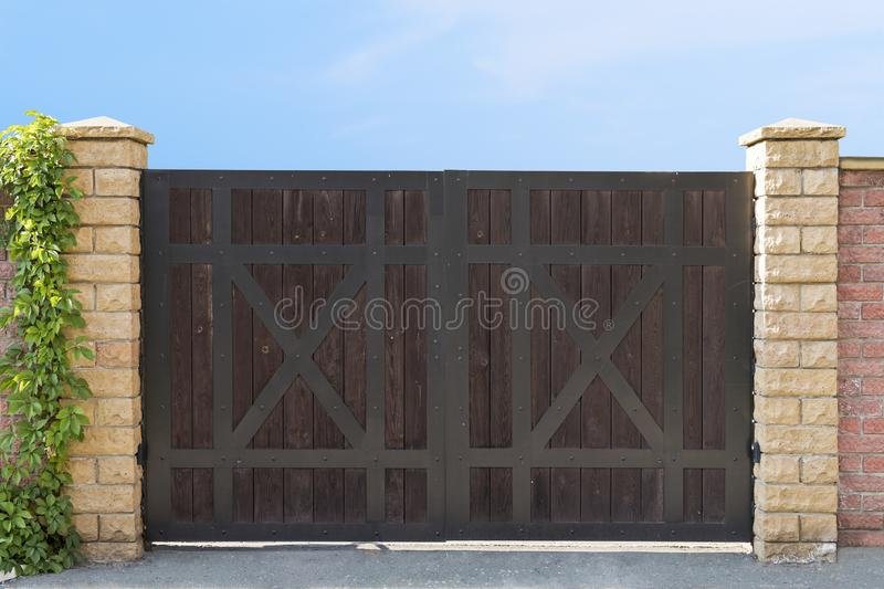A close up of a driveaway dark wood closed gates at the clear blue sky background. Entry gate of a country house. Driveaway gates. A close up of a drive away royalty free stock image