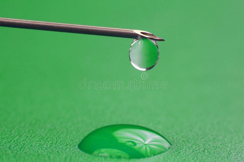 Close-up of a drop of medicine on the tip of a medical injection needle. The close-up of a drop of medicine on the tip of a medical injection needle royalty free stock images