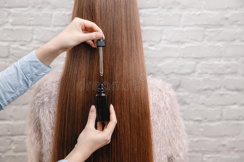 Close-up drop oil restore and recovery hair is applied to head bulbs. Concept hairdresser spa salon royalty free stock photos