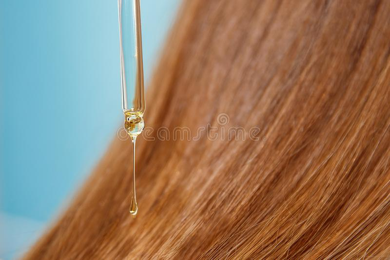 Close-up drop of oil restore and recovery hair is applied to head bulbs. hairdresser spa salon. stock photos