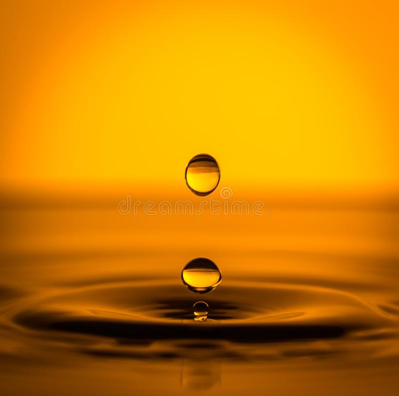 Golden Drops Falling on Water. Close-up of drops falling onto a water surface, raising circular waves, in a golden light. The drops refract the light like lenses royalty free stock photo