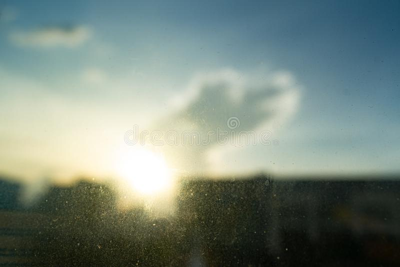 Close up dry water and stains on glass wall with blue sky, clouds and sunshine background. royalty free stock image