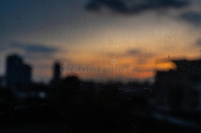 Close up dry water and stains on glass wall with twilight sky, clouds and shadow of buildings background. stock image