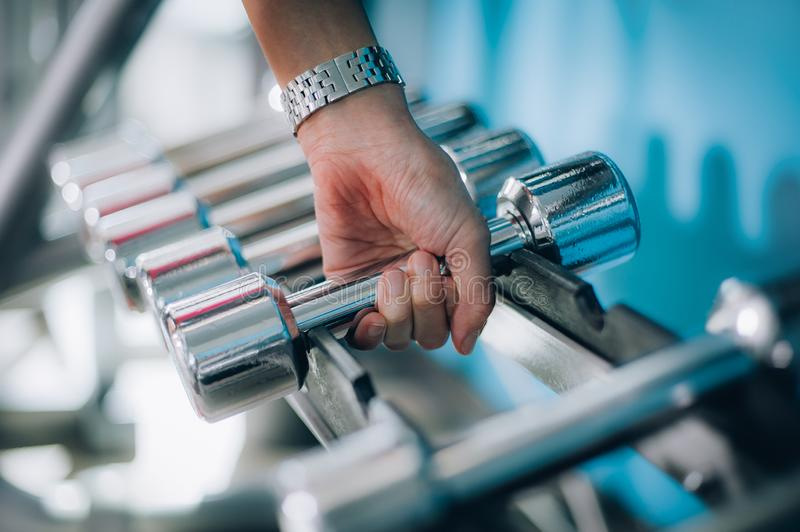 Close up of dumbbells in woman hand. Power fitness, sport, training, lifestyle royalty free stock photo