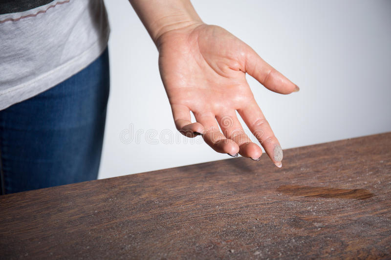 Close-up of dust on woman finger. Taken from wooden table stock photography
