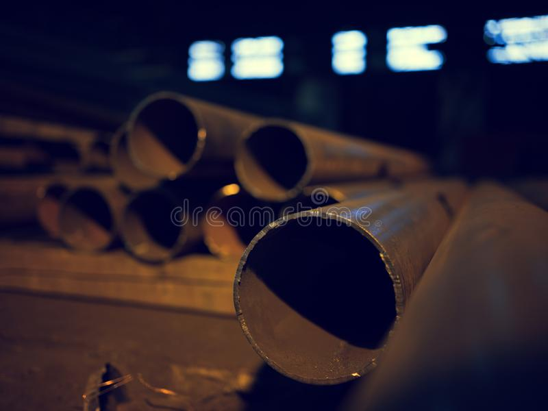Close up of dusty old metal tubes on factory floor. Close up of dusty old metal tubes lying on factory floor on blurred background of windows. Dark industrial royalty free stock photography