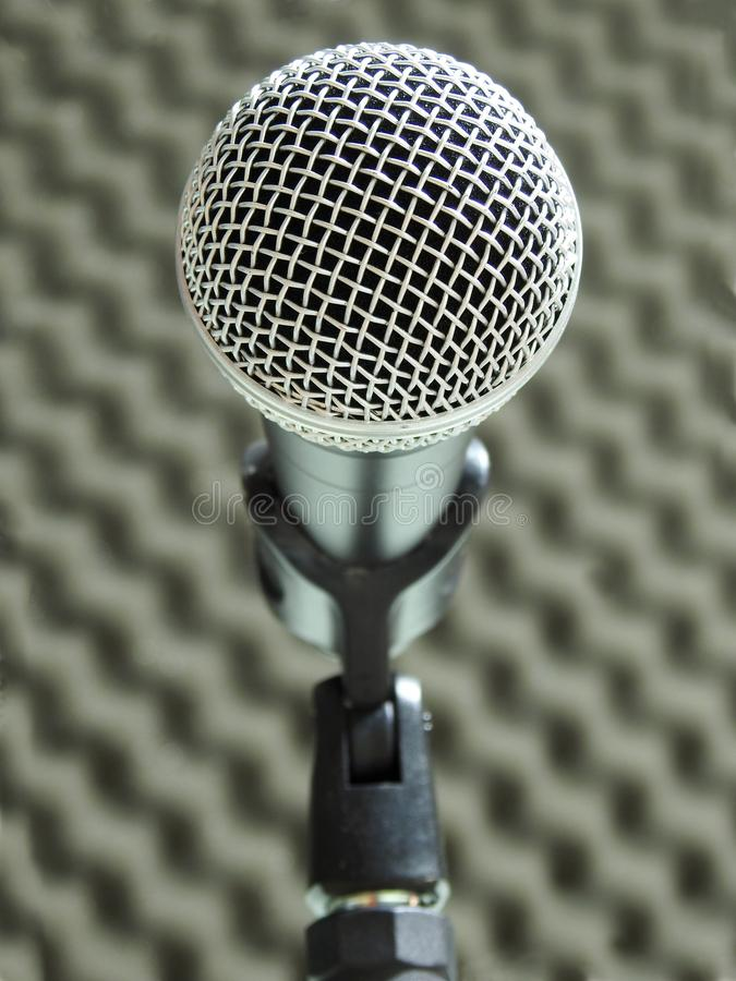 Close-up of a dynamic vocal microphone. Blurred background of acoustic foam. royalty free stock photos