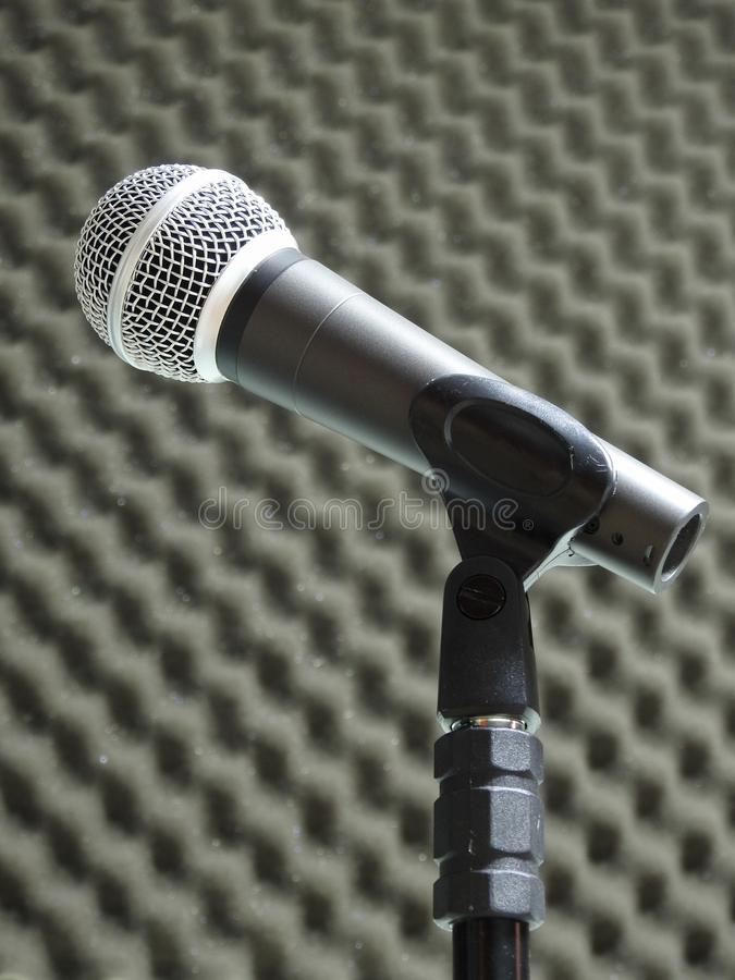 Close-up of a dynamic vocal microphone. Blurred background of acoustic foam. royalty free stock image