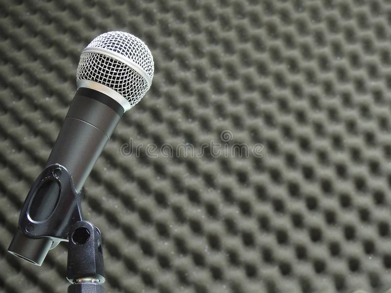 Close-up of a dynamic vocal microphone. Blurred background of acoustic foam. royalty free stock images