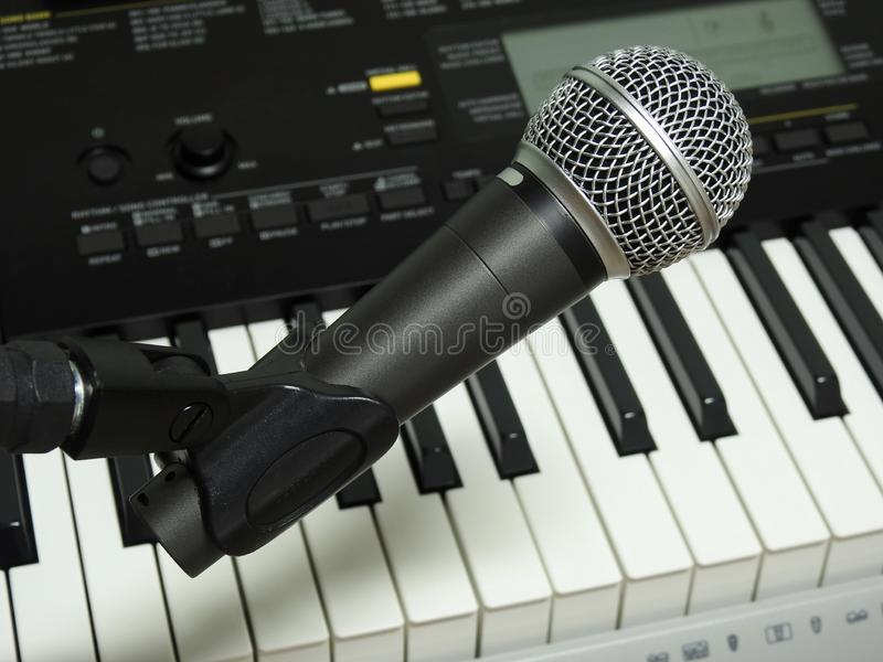 Close-up of a dynamic vocal microphone and a digital keyboard. royalty free stock photography