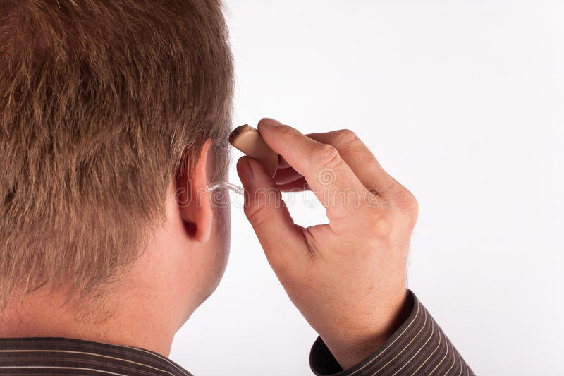 Close up ear of a man inserting a hearing aid royalty free stock image