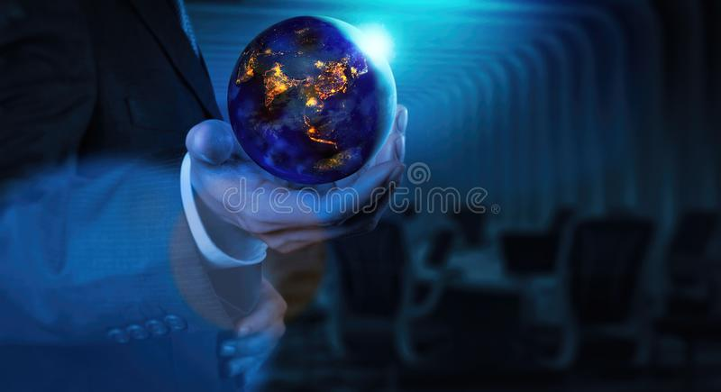 Close up of Earth at night was holding in businessman hands for Earth day and Energy saving concept royalty free stock image