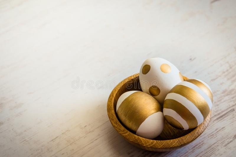 Close up of easter eggs colored with golden paint in a wooden plate. Various striped and dotted designs. White wooden background. royalty free stock photo
