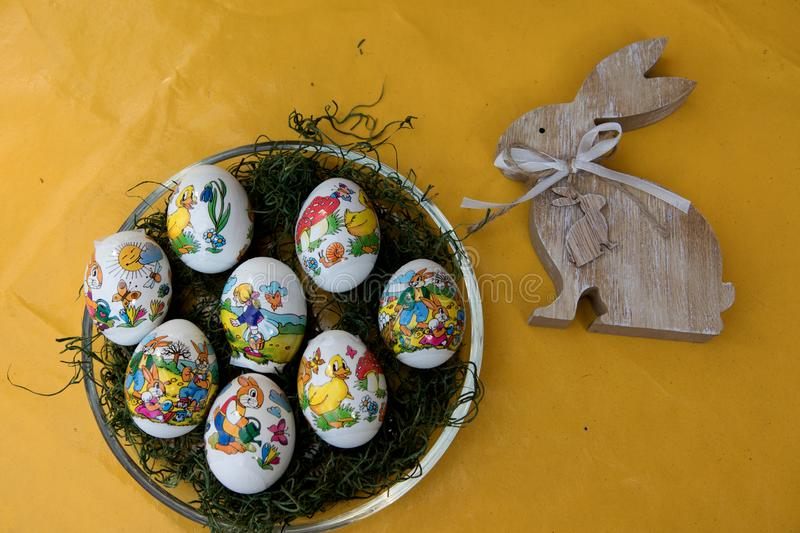 Close up on easter eggs and a wooden easter bunny on a yellow tablecloth with copy space royalty free stock photo