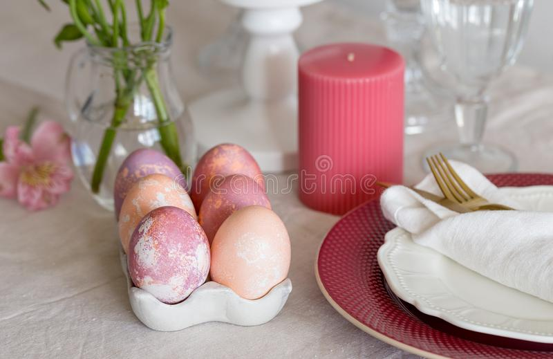 Close up Easter multicolored eggs at concrete stand for eggs on table royalty free stock photography