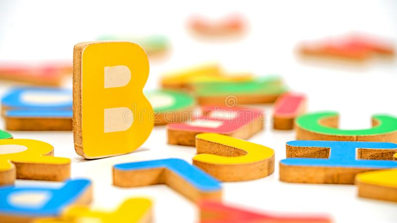 Close up education toys wooden scrabble Alphabet B letters. Macro photography isolated on white background stock image