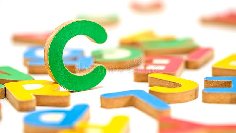 Close up education toys wooden scrabble Alphabet C letters. Macro photography isolated on white background royalty free stock photography