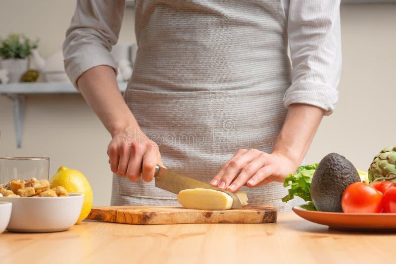 Close-up Een chef-kok snijdt mozarellakaas of feta, beweegt, in de loop van een vegetarische salade in de huiskeuken Lichte achte royalty-vrije stock foto