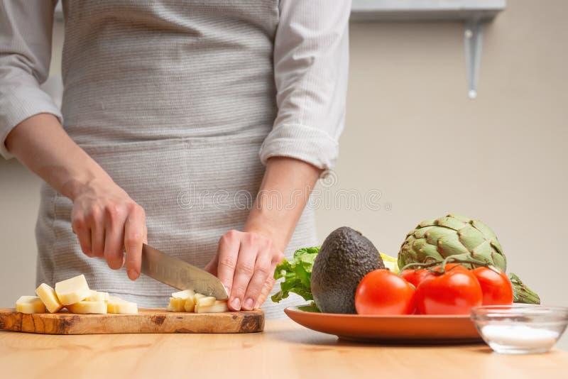 Close-up Een chef-kok snijdt mozarellakaas of feta, beweegt, in de loop van een vegetarische salade in de huiskeuken Lichte achte royalty-vrije stock foto's