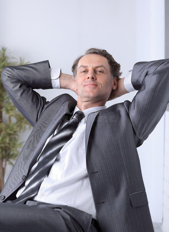 close-up een succesvolle zitting van zakenmanrelaxarea achter een Bureau stock afbeeldingen