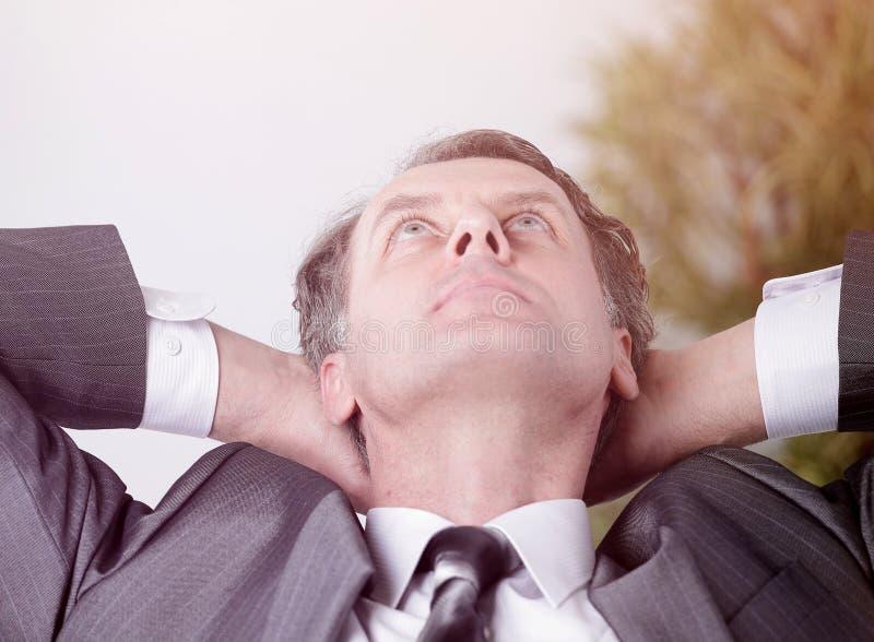 close-up een succesvolle zitting van zakenmanrelaxarea achter een Bureau stock fotografie