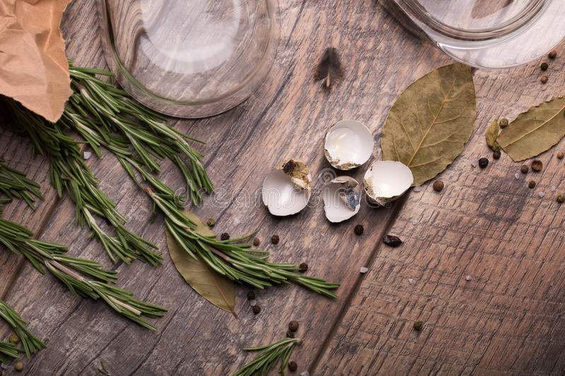 Close-up of egg shell, a glass container for butter, and rosemary, twigs. Food ingredients on a wooden table background. stock photo