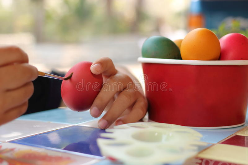 Close up eggs are being painted with child for preparing easter day. Selective focus and shallow depth of field. royalty free stock photo