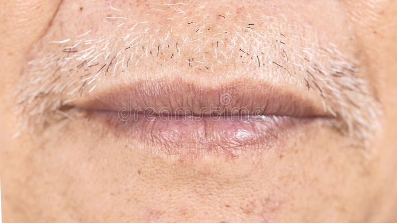 Close-up of elderly asian man mouth with wrinkle on face stock photography