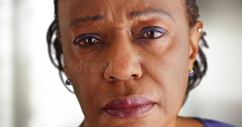 A close-up of a elderly black woman looking sad stock images