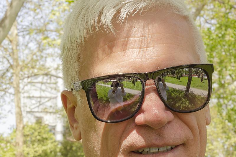 Close-up of an elderly gray-haired man in mirrored sunglasses . royalty free stock photos