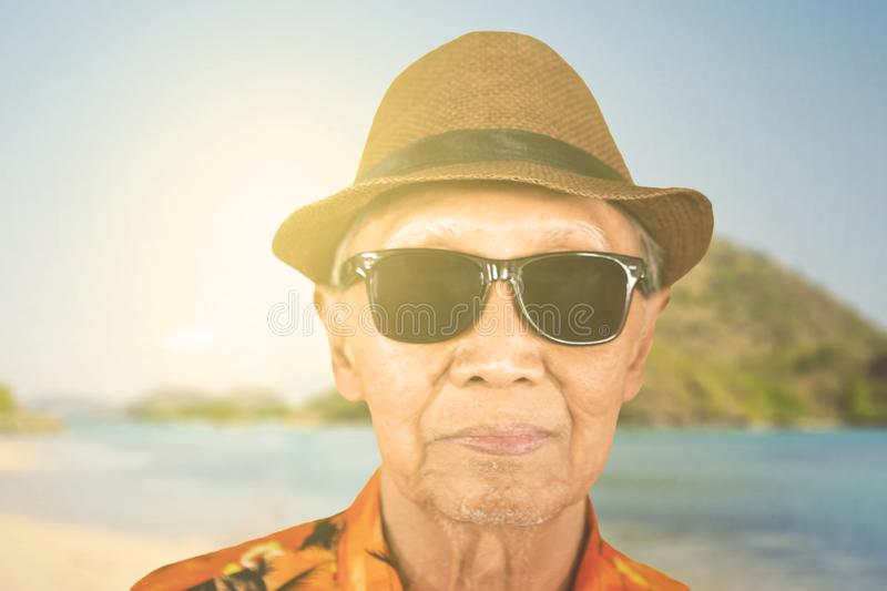 Elderly man wearing sunglasses on the beach stock photography