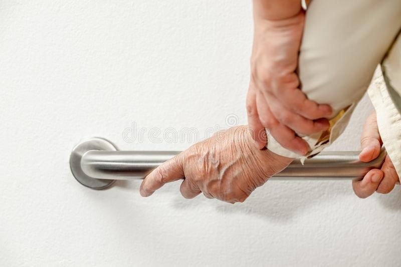 Elderly woman holding on handrail with caregiver. Close up elderly woman holding on handrail with caregiver stock images