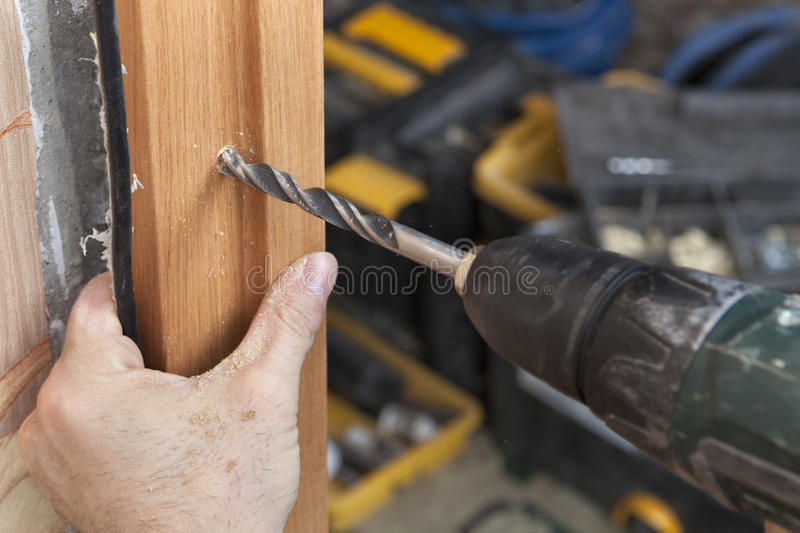 Close up of an electric drill drilled hole in doorjamb. royalty free stock images