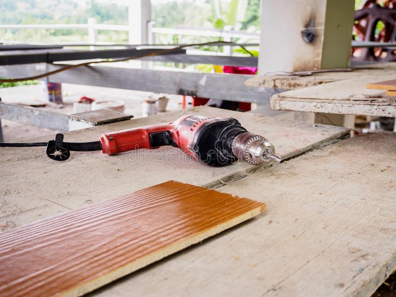 Close up electric drill at work site. On wooden board stock image