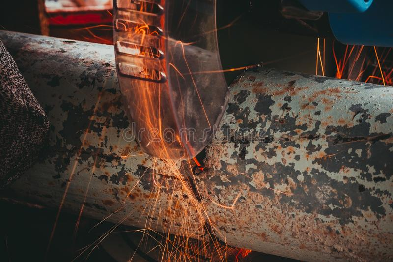 Close-up of Electric Grinder Cutting metal pipe with Bright Sparks tails royalty free stock photo
