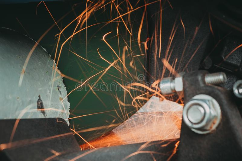 Close-up of Electric Grinder Cutting metal pipe with Bright Sparks tails stock photos