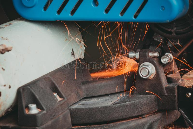 Close-up of Electric Grinder Cutting metal pipe with Bright Sparks tails stock images