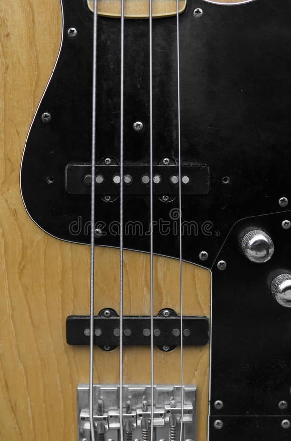 Close up of electrical bass guitar fingerboard. Wooden bass with volume controller. stock images