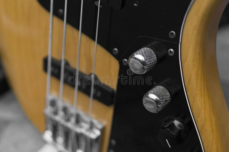 Close up of electrical bass guitar fingerboard. Wooden bass with volume controller. stock photo