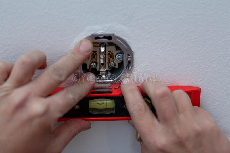 Close up of electrician at work on switches and sockets of a res stock photography